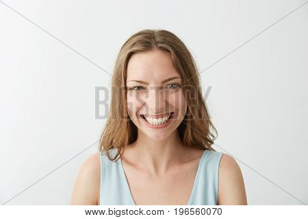 Beautiful sincere happy girl smiling laughing looking at camera over white background. Copy space.
