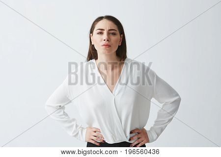 Portrait of displeased young businesswoman with arms akimbo looking at camera over white background. Copy space.