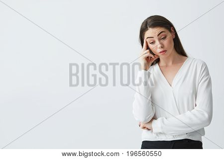 Displeased young beautiful businesswoman thinking looking down with finger near temple over white background. Copy space.