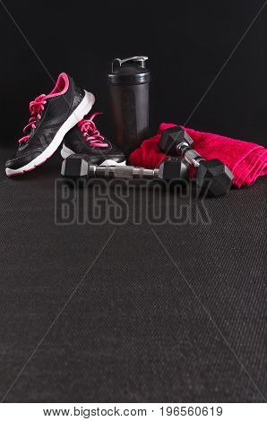Fitness female outfit background copy space. Sneakers, dumbbells, towel and water bottle. Active lifestyle, body care concept