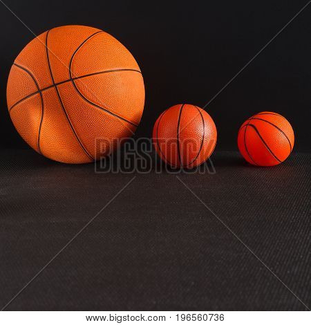 Big and small basketball balls on black background copy space. Active game, healthy lifestyle, streetball concept