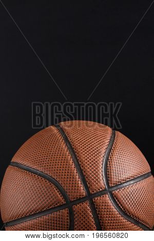Old basketball ball on black background copy space. Active game, healthy lifestyle, streetball concept