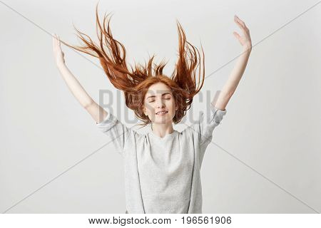 Portrait of young cheerful beautiful redhead girl smiling with closed eyes shaking hair over white background. Copy space.