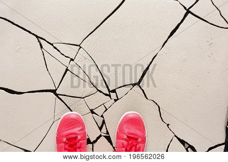 Top view of pink shoes on cracked floor, copy space. Unrecognizable person in sneakers standing on fractured background