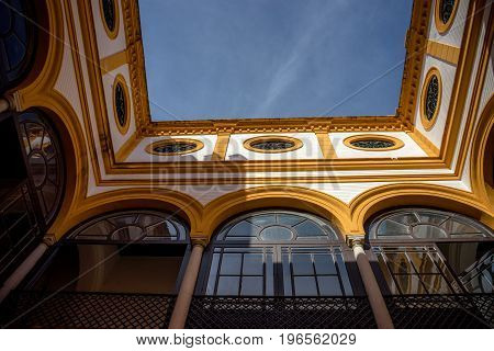 Yellow Arch Of A Balcony Against A Blue Sky In Seville, Spain, Europe