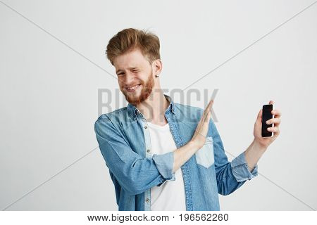Displeased young handsome man showing stop sign to phone in another hand looking at camera resisting over white background. Copy space.