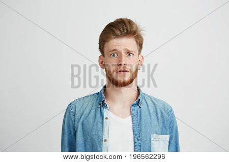 Young handsome guy looking at camera naively hopefully over white background. Copy space.