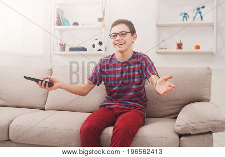Favorite TV show. Teenager with remote panel watching TV while sitting on the couch in living room at home