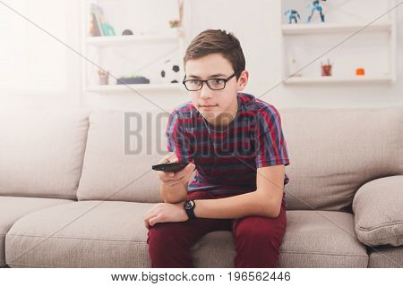 Teenager boy watching television, using TV remote control while sitting on couch in living room at home