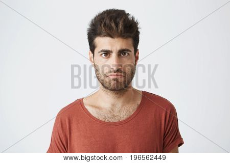 Bearded stylish male having displeased look standing in casual cloth against white background. Young man having some problems looking with unsatisfaction and discontent into camera.