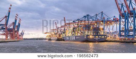 HAMBURG , GERMANY - JULY 12 2017: Container gantry cranes of the terminal Burchardtkai unloading ships in the deepwater port Hamburg-Waltershof at night