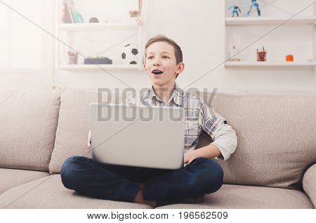 Happy boy with computer on sofa at home. Child in braces excited at what he sees on the web