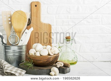 Fresh champignons in a wooden bowl on the background of a kitchen white brick wall with cutting boards, kitchen utensils, tools, olive oil for cooking dinner. Selective focus