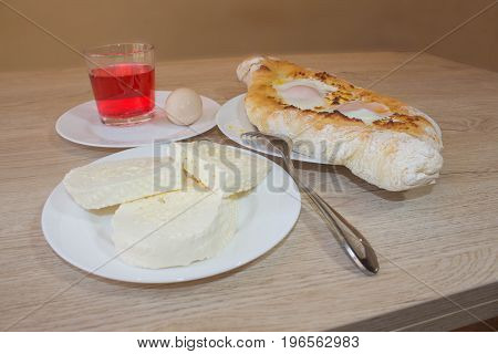 Adjarian Georgian national dish Khachapuri bread with cheese and egg on a plate in a cafe. Khachapuri raditional Georgian cheese-filled bread Ajarian style