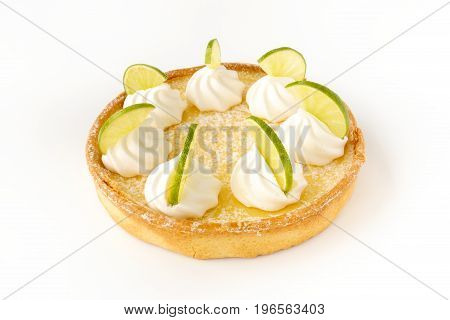 Closeup of a homemade lemon tart decorated with meringue swirls and lime slices on white background.