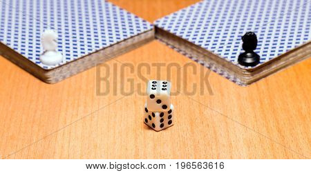 Objects for popular board games for every taste on the wooden surface dices playing cards and chess pieces of horses