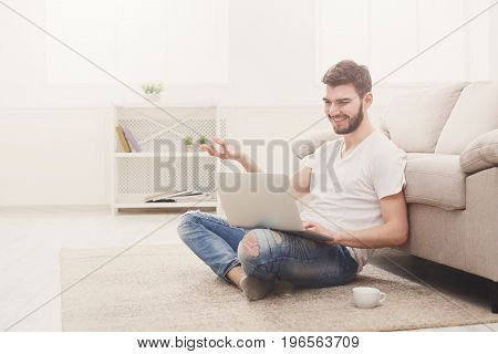 Young man having video call on laptop. Boy in casual talking, smiling and gesturing on the floor in light appartment, copy space