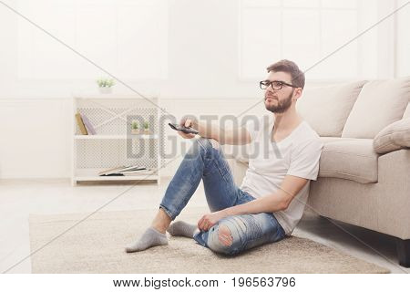Young tired man watching tv. Sitting on the floor, pointing with remote controller on tv-set, copy space