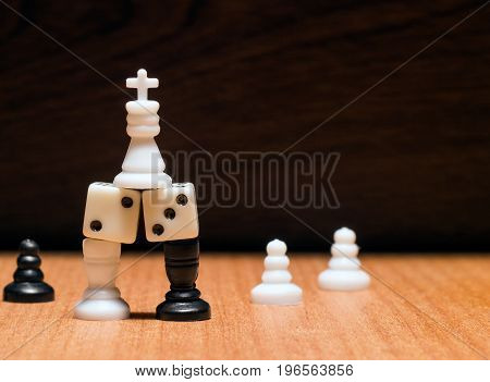 The white king on top he stands on the dice that the rooks are holding behind them are pawns on a wooden background