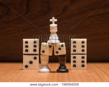 The chess king stands on dice that are on the rooks on a wooden background objects for table games popular all over the world