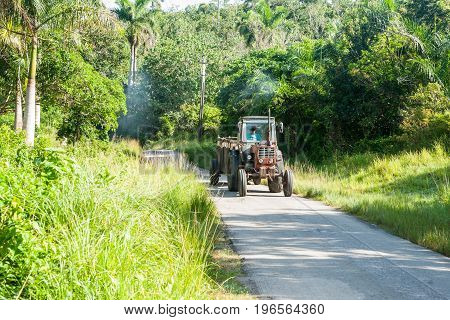 Puffs of smoke follow typically old tractor along narrow rural road in Cuba.