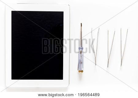Daignostic of gadgets. Tablet computer and tools on white background top view.