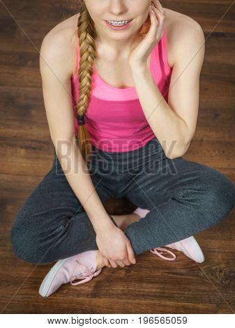 Woman In Sportswear Sitting On Ground