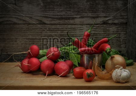 Red white, yellow vegetables lie on a wooden Board. Useful products. Diet, natural, healthy food. In a rustic style.