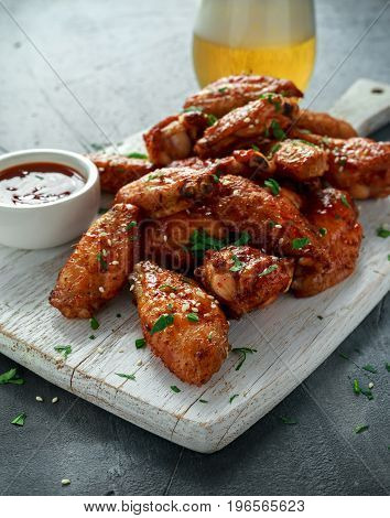 Baked chicken wings with sesame seeds, beer and sweet chili sauce on white wooden board