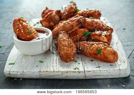 Baked chicken wings with sesame seeds and sweet chili sauce on white wooden board