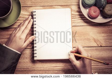 Top view of businesswoman sitting at wooden table and writing in notepad