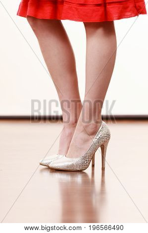 Close up on woman feet wearing elegant white high heels shoes and red dress. Footwear trends concept.