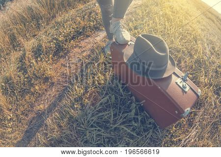 Young woman puts foot on brown vintage suitcase in the field road during summer sunset. Toned image and travel concept.