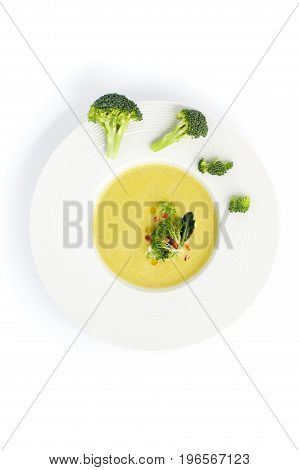 White Plate With Cream Of Broccoli Soup, Served With Pine Nuts On A Light Background..