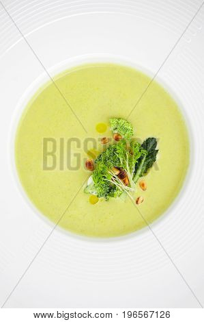 Cream Of Broccoli Soup, Served With Pine Nuts Close-up In A White Plate..