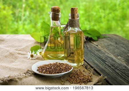 Vegetable oil of buckwheat. Buckwheat oil on a wooden table. Side view.