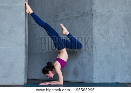 Slim female yogi wearing sportswear performing inversion or arm balance standing upside down on forearms.