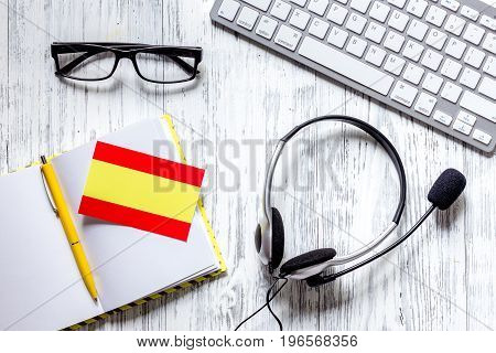 Learning languages online. Spanish. Headphones and keyboard on wooden table background top view.