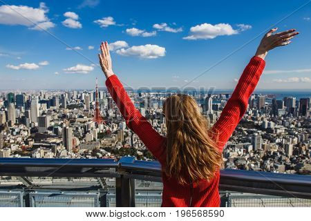 Happy young woman with her hands up. Girl stands with her back. Tokyo Tower with skyline on background.