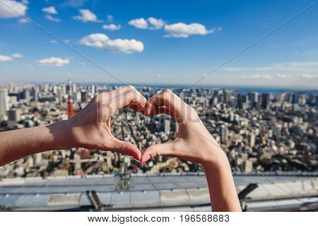 Female hands In form of heart against Tokyo with skyline in Tokyo Japan.