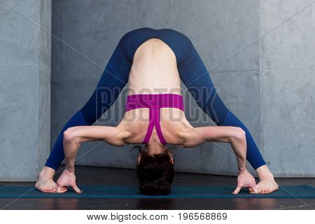 Full-length front view of sporty young woman practicing yoga doing standing straddle forward bend pose, Prasarita Padottanasana, working-out indoors.