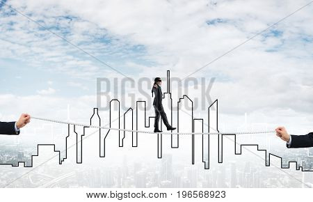 Businessman with blindfolder on eyes walking on rope over cityscape background