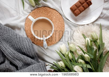 A cup of coffee next to a bouquet of tulips lies on a cozy tablecloth