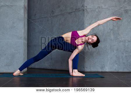 Slim Caucasian girl standing in side angle pose, parsvakonasana, during her yoga routine in gym.