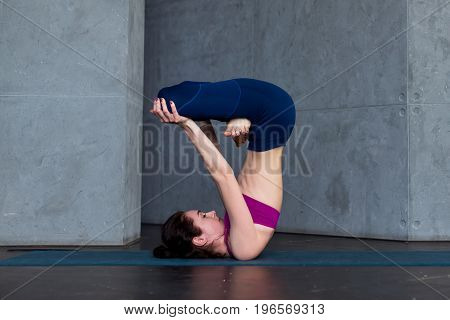 Advanced young yogini practicing Hatha yoga standing in inverted lotus pose, padmasana, on mat.
