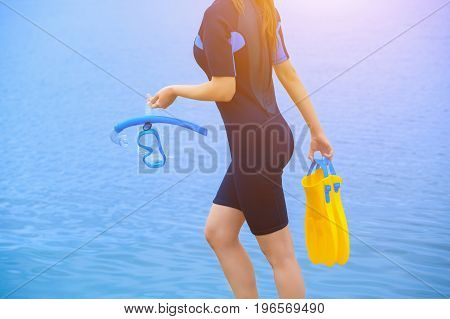 A girl diver in a wet suit holds a mask with a blue tube in her hands and a yellow fin in the other hand.