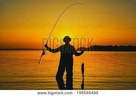 A fisherman with a fishing rod in his hand and a fish caught stands in the water against a beautiful sunset.