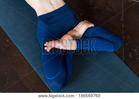 Cropped image of female legs lying in lotus yoga pose on mat indoors.