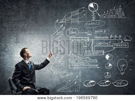 Young businessman sitting in chair and business sketches on wall