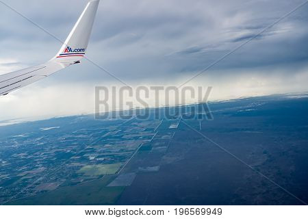 Florida, USA - July 9, 2012; AA.com red and blue brand on aircraft wing above cloud and against dark clouds with urban land below
